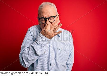 Middle age handsome hoary man wearing casual striped shirt and glasses over red background smelling something stinky and disgusting, intolerable smell, holding breath with fingers on nose. Bad smell