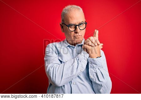 Middle age handsome hoary man wearing casual striped shirt and glasses over red background Holding symbolic gun with hand gesture, playing killing shooting weapons, angry face