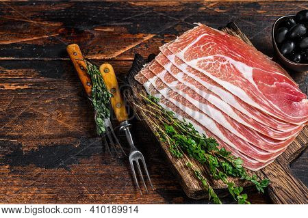 Traditional Spanish Sliced Jamon Serrano Ham On A Cutting Board. Dark Wooden Background. Top View. C