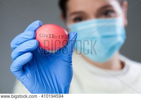 Sad Young Woman Wearing Protective Face Mask And Medical Gloves Holding A Red Easter Egg With Covid-