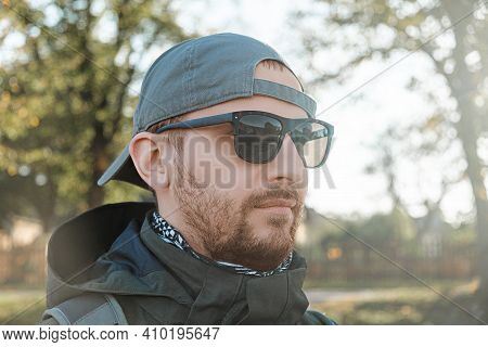 Bearded Man In Sunglasses And A Baseball Cap On The Background Of Trees And Nature On A Sunny Autumn