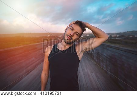 Healthy Young Man Stretching Before Or After Exercises At Sunset Or Sunrise. Fitness Athlete In Blac