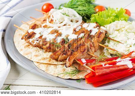 Grilled Chicken Kebab With  Pita, Fresh Vegetables On A White Table.  Grilled Meat Skewers, Shish Ke