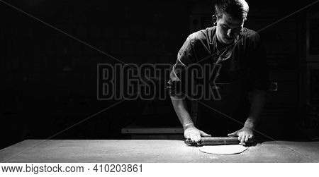 A Male Chef Rolls Out Thin Pizza Dough On A Table In A Pizzeria. Banner And Black Background.