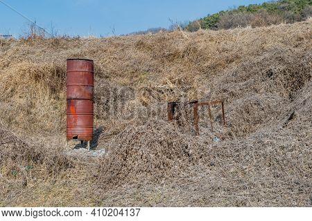 Two Rusty Metal Barrels Used As Incinerator In Rural Area.