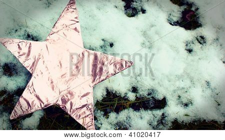 Pink aluminium foil star in snow and grass
