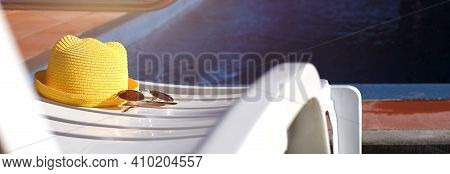 Beach Accessories A Yellow Hat And Sunglasses Lie On A White Deck Chair By The Pool. Sun Protection,