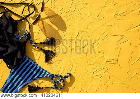 Blue With Black Stripes Female Swimsuit And Sunglasses On A Yellow Background. The Concept Of A Beac