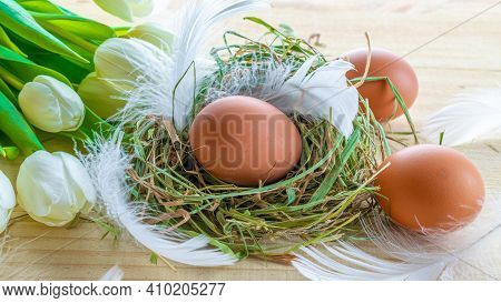 Easter Eggs Basket. Natural Colour Egg In Basket With Spring Tulips, White Feathers On Wooden Table