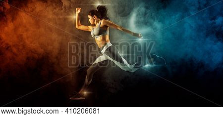 Sporty young woman running on smoke background. Sports banner. Horizontal copy space background
