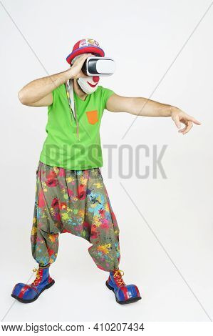 Holiday And Fun Concept. The Clown Is Playing, He Has Virtual Glasses On His Head, He Looks Like Thr