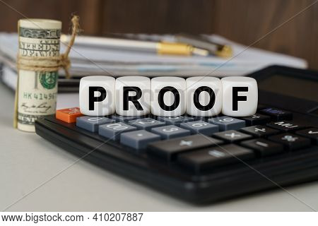 Business And Finance Concept. There Are Cubes On The Calculator That Say - Proof. Nearby Out Of Focu