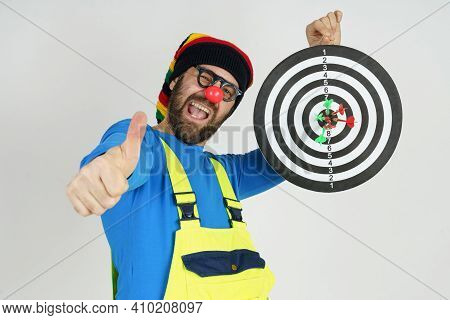Celebration And Communication Concept. The Clown Holds A Target In His Hands, Shows The Result Of Da