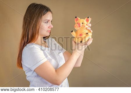 A Girl 14-15 Years Old Is Holding A Piggy Bank And Looking At It. Selective Focus.