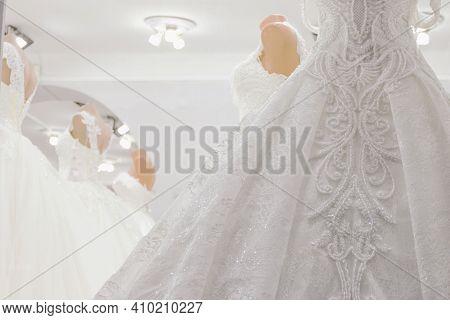 Wedding Dresses On Mannequins At Shop. Interior Of Bridal Salon. Defocused Photo With Soft Focus.