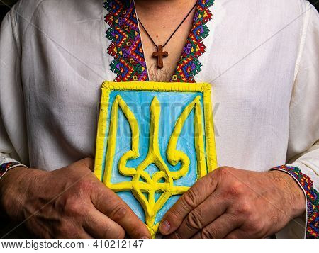 26/02/2021. Kyiv, Ukraine. Coat Of Arms Of Ukraine In The Hands Of A Person With A Pectoral Band. Em
