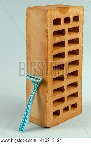 Plastic Razor And Red Brick On A Blue Background. A New Blue Razor Is Leaning Against A Vertical Bri