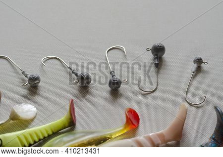 Random Jig Heads And Fragments Of Rubber Lures Lie On A White Textured Background. A Special Device