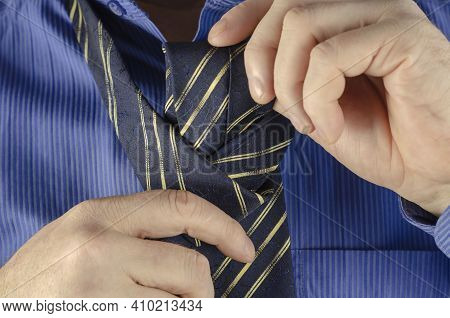 An Adult Man In A Blue Shirt Is Tying A Tie. Male Hands With A Blue Tie With A Yellow Stripe. Step B