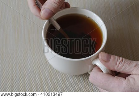 A Man's Hand Is Stirring Black Tea In A Mug With A Metal Spoon. A White Ceramic Mug Full Of Black Te