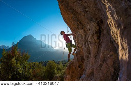 Athletic Man Climbs An Overhanging Rock With Rope, Lead Climbing. Silhouette Of A Rock Climber On A