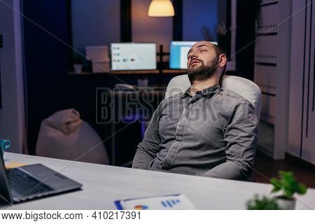 Young Businessman Resting On Chair While Working On Deadline. Workaholic Employee Falling Asleep Bec