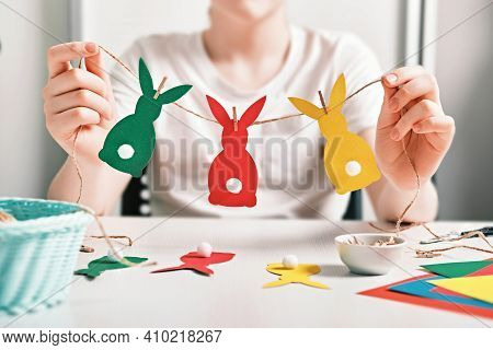 Diy Easter Home Decor. Happy Boy Make Garland Of Colored Paper, Twine And Pom-poms. Selective Focus