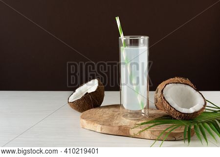 Coconut Water In A Glass With Straw On White Wooden Table Over Brown Background. Fresh Detox Coconut