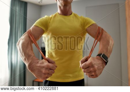 Athletic 46-year-old Man Training At Home On Self-isolation. Athlete Exercising At Home With An Elas