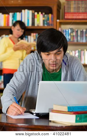 Student - Young Asian man in library with laptop learning, a female student standing in the Background on a shelf reading book