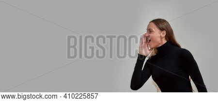 Joyful Young Caucasian Woman Dressed In Black Smiling Away And Screaming, Telling Sale Information,