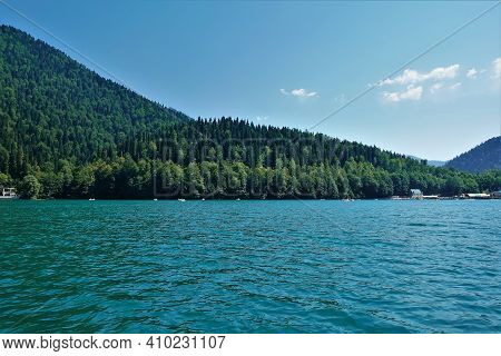 The Alpine Lake Ritsa Is Surrounded By Wooded Mountains. Tourist Boats Float On The Turquoise Surfac