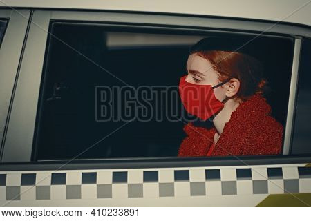 Young Woman Passenger Takes A Ride By Taxi Car During The Coronavirus Pandemic Quarantine. Woman Wea
