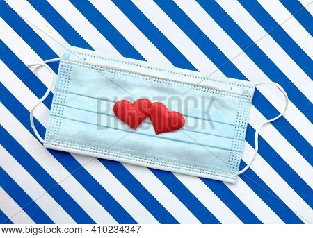 Disposable Medical Mask On Striped Blue  White Background With Red Hearts On It Against Bacteria And