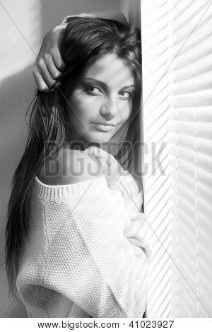 Beautiful young brunette woman in white near window