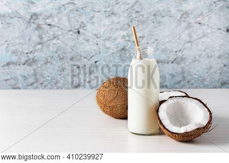 Coconut Vegan Milk In A Bottle With Coconut Halves On Wooden Table. Alternative Vegan Nut Milk.