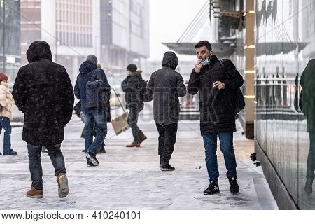 Moscow. Russia. February 12, 2021. A Man In A Medical Mask Smokes On The Street During A Snowfall Am