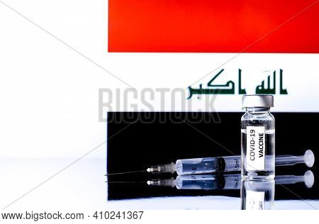 Vial With Covid Vaccine And Syringe. Iraqi Flag In The Background