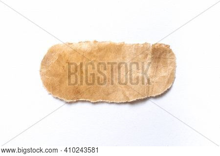 Close Up Of A Ripped Piece Of Brown Spaper On White Background
