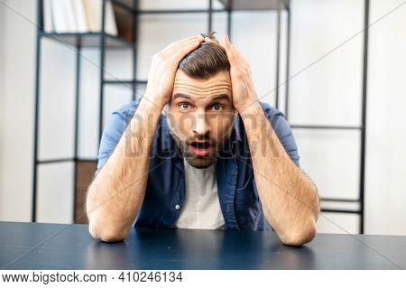Troubled Young Hipster Bearded Guy Employee With Open Mouth Is Sitting At The Desk And Holding Head