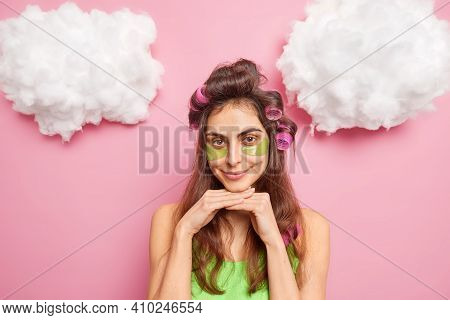Pretty Dark Haired Young Woman With Hair Curlers Makes Hairstyle Applies Collagen Patches Under Eyes
