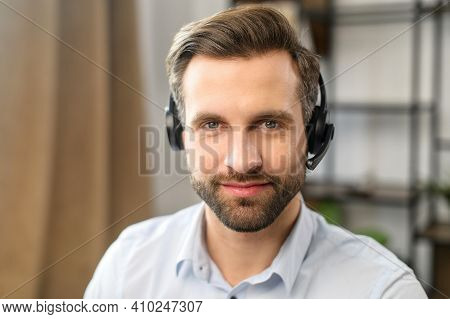 Positive Young Handsome Bearded Man Employee In Headset With Microphone, Working In The Customer Ser