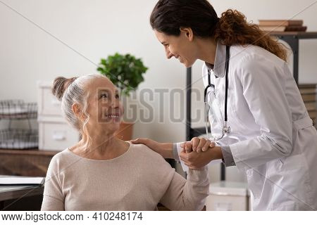 Smiling Mature Patient And Female Doctor Holding Hands, Good News