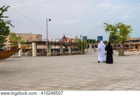 Doha, Qatar - Nov 20. 2019. Man And A Woman In National Clothes Are Walking Along Embankment In Kata