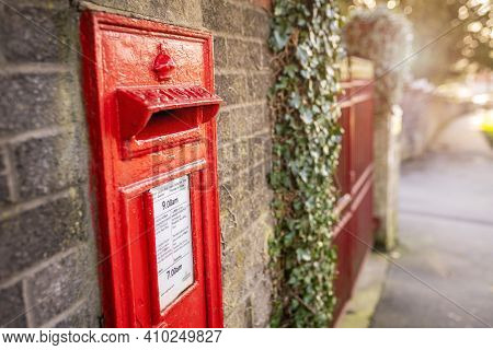 Swansea, Wales, Uk - February 25, 2021: Classic British Red Royal Mail Mailbox For Letters On A Wall