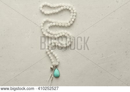 Rosary Mala 108 Beads From Natural Stones Moonstone Lie On Light Modern Background. Author's Jewelry