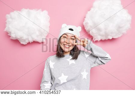 Portrait Of Happy Asian Girl Dressed In Slumber Suit Shows Peace Gesture Near Life Enjoys Life Smile