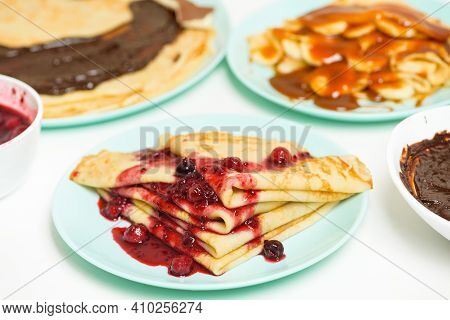 Blini Pancakes With Red Berry Jam Close-up On A Blue Plate On A Light Background . Traditional Russi