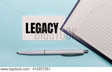 On A Light Blue Background, An Open Notebook, A White Pen And A Card With The Text Legacy. View From