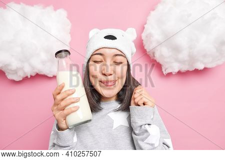 Satisfied Asian Girl Licks Lips As Holds Bottle Of Her Favorite Milk Keeps Eyes Closed Raises Clench